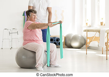 Elderly woman sitting on ball