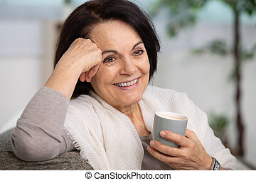 elderly woman sitting on sofa holding a cup of coffee