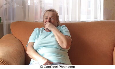 Elderly woman sitting on the couch strongly coughing