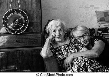 Elderly woman sitting on the couch with his adult daughter.