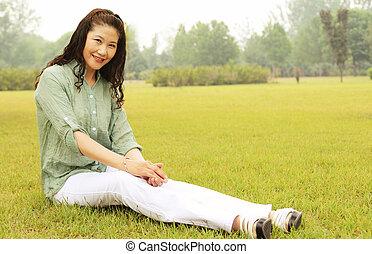 elderly woman sitting outside the lawn