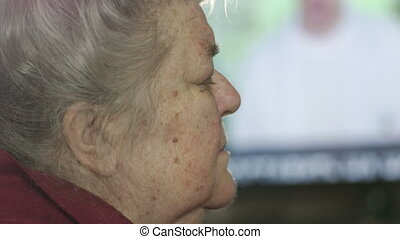 Elderly woman sleeping in front of TV