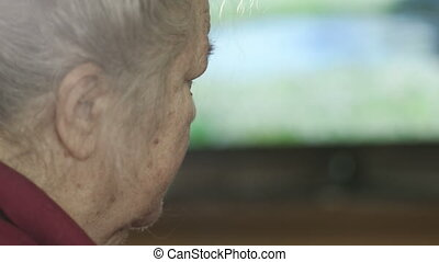 Elderly woman sleeping in front of TV.