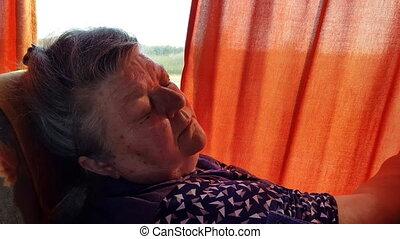 Elderly woman sleeping on the bus beside the window in a long journey.