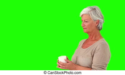 Elderly woman smelling her coffee - Chroma-key footage of an...