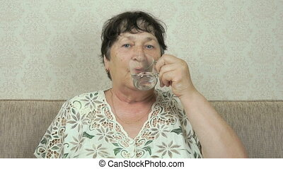 Elderly woman smiles and drinks water from a glass