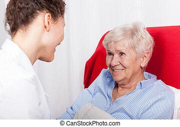 Elderly woman smiles to nurses