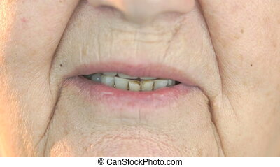 Elderly woman smiling with false teeth. Close up - The...