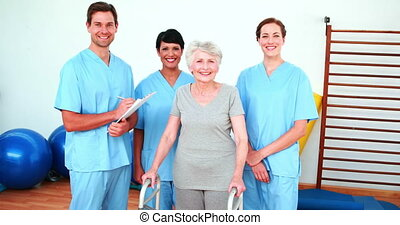 Elderly woman smiling with her rehab team