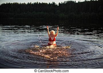 Elderly woman splashing in the summer river at village.