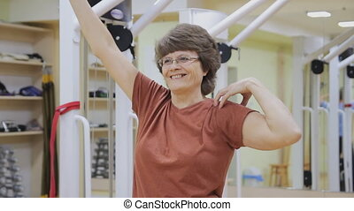 Elderly woman stretching out, doing physiotherapy exercises in fitness room. Healthy gymnastics. Active seniors.