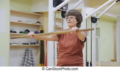 Elderly woman stretching out, doing physiotherapy exercises with stick in fitness room. Healthy gymnastics. Active seniors.