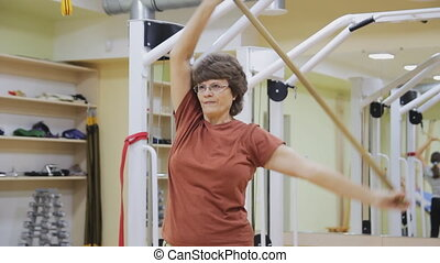 Elderly woman stretching out, doing tilt exercises with stick in fitness room. Healthy gymnastics. Active seniors.