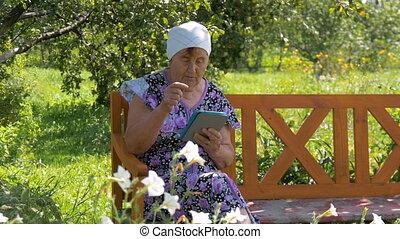 Elderly woman studying web tablet