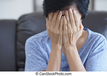 Elderly woman suffering from headache Depressed  at home