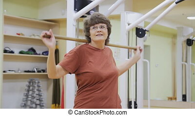 Elderly woman swinging with stick, doing physiotherapy exercises in fitness room. Healthy gymnastics. Active seniors.