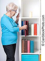 Elderly woman taking off photo album from shelf