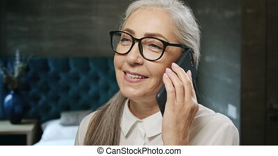 Elderly Woman Talking on Smartphone - Charming retired...