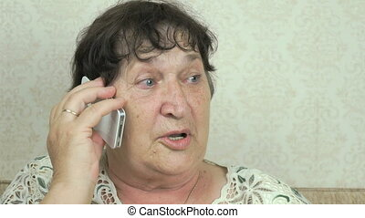Elderly woman talking on the phone at home