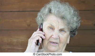 Elderly woman talking on the smartphone phone