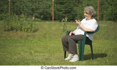 Elderly woman talking using a smart phone outdoors
