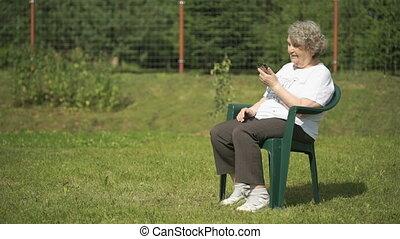 Elderly woman talking using a smart phone outdoors