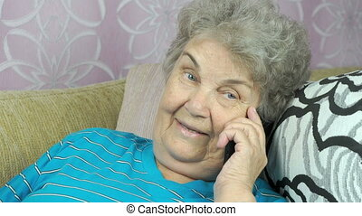 Elderly woman talking with friend on mobile phone
