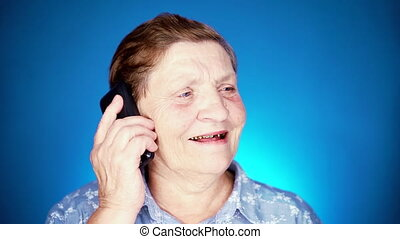 Elderly woman talking with mobile device on blue studio wall. Grandmother smiling, have pleasant conversation. slow motion