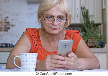 Elderly woman texts on mobile phone - Elderly woman texts on...