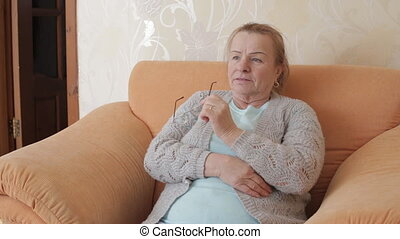 Elderly woman took off her glasses and watches TV