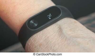 Wristband of heart rate monitor. The elderly woman touches and looks at the wristband of pulse monitor indoors