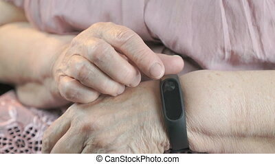Elderly woman touches wristband of pulse monitor - Wristband...
