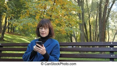Elderly woman typing a phone message while sitting at the autumn park. Happy old woman looking at screen on smartphone. Senior woman using wireless internet connection on smart phone in slow motion.