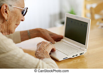 Elderly woman typing on laptop computer