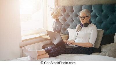 Elderly Woman Typing on Laptop in Bedroom