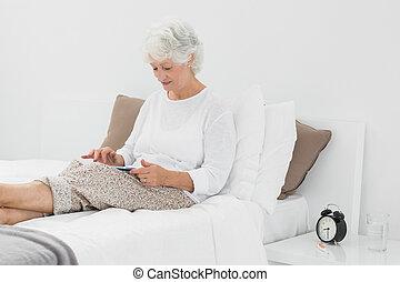 Elderly woman using a digital tablet