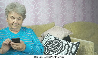 Elderly woman using a mobile phone sits on a sofa