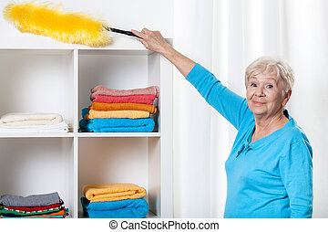 Elderly woman using duster - Smiley elderly woman using...