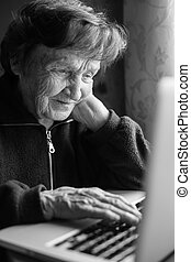 Elderly woman using laptop computer at home (black and white photo)