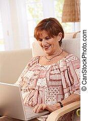 Elderly woman using laptop computer
