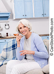 Elderly woman using mobile phone at home