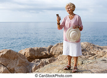 Elderly woman using phone at seaside