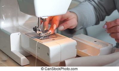 Elderly woman using sewing machine. - Elderly woman using...