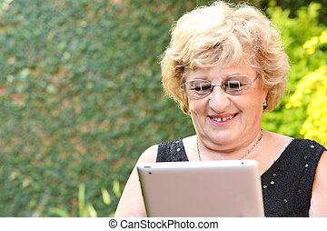 Elderly woman using tablet.
