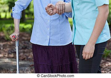 Elderly woman walking holding a nurse