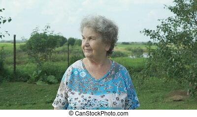 Elderly woman walking in the park of garden