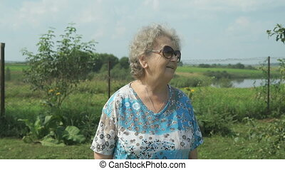 Elderly woman walking in the park of garden