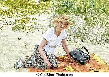 elderly woman walking near the sea