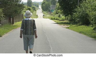 Elderly woman walking on the road in the village