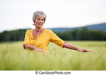 elderly woman walking though field